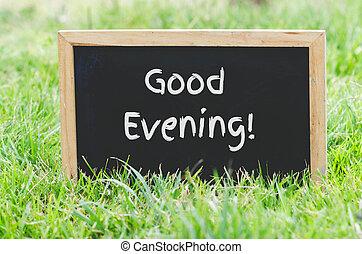 Good evening message on blackboard on green grass.