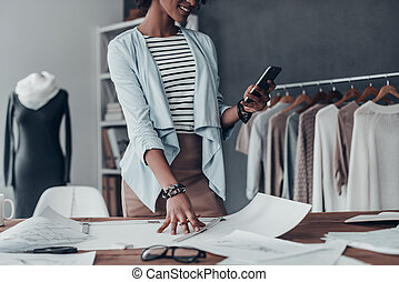 Good feedback from client. Close-up of young African woman holding a smart phone and smiling while standing in her studio near the clothes hanging on the racks