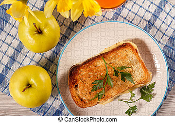 Good food for breakfast. Toast with butter and cheese. Glass of juice and apples