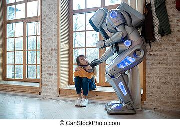 Big house robot touching girls shoulder tenderly