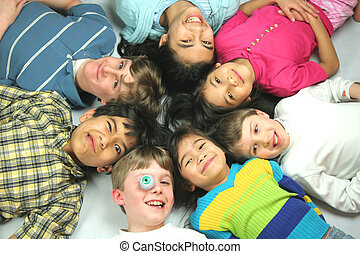 Seven good friends lying in a circle just having fun and making faces for the camera. A green toy eyeball is used as a prop for fun. Caucasian and asian backgrounds. Ages from 5 to 13.
