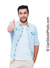 Good job! Happy young Indian man showing his thumb up and smiling while standing against white background