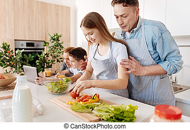 Pleasant caring father teaching his daughter to cook