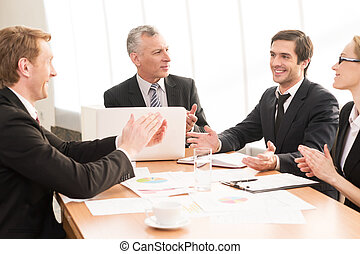 Good job! Three business people in formalwear applauding to their colleagues while sitting together at the meeting