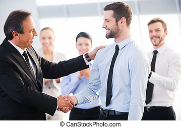 Good job! Two cheerful business men shaking hands while their colleagues applauding and smiling in the background