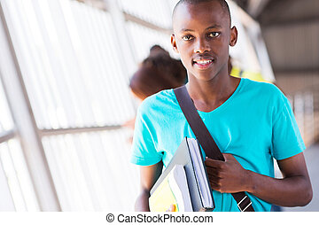 african american college boy holding books