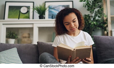 Good-looking African American student is reading book and...