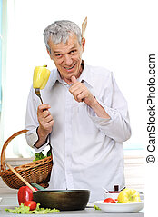 Good looking aged man cooking in kitchen