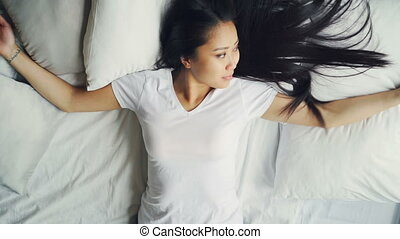 Good-looking Asian brunette in white T-shirt is lying down...
