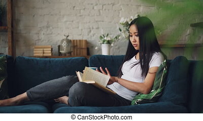 Good-looking Asian woman is reading book enjoying modern...