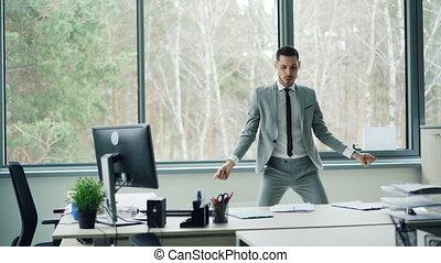 Good-looking bearded man in suit is dancing in office room...