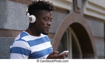 Good looking black man listening music on street - Good...