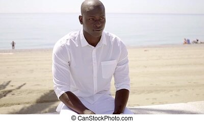 Good looking black model seated near sandy beach and ocean...
