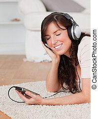 Good looking brunette female listening to music with her mp3 player while lying on a carpet in the living room