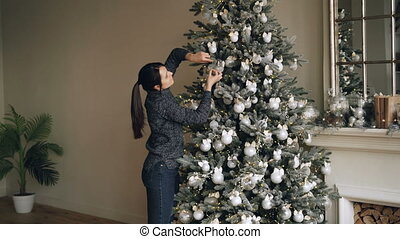 Good-looking brunette is decorating fir-tree with beautiful balls and lights enjoying festive activity on winter holidays. Decorated mantel and fireplace are visible.