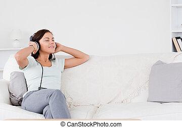 Good looking brunette listening to music in her living room