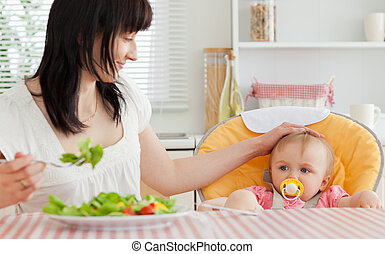 Good looking brunette woman eating a salad next to her baby