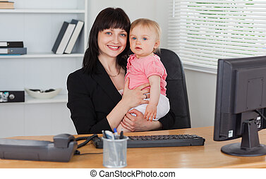 Good looking brunette woman posing while holding her baby on her knees in the office