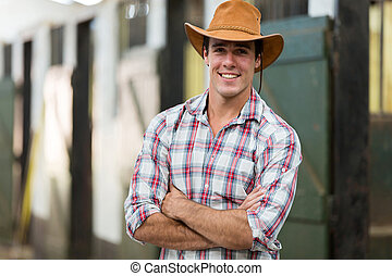 cowboy with arms crossed in stable - good looking cowboy...