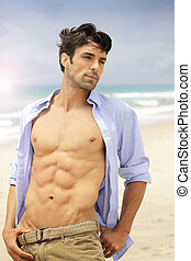 Good looking young fit male on beach with open shirt and muscular body with abs