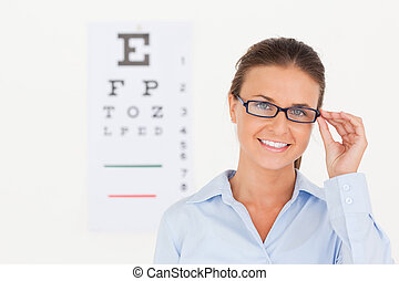 Good looking eye specialist wearing glasses looking into the camera in her surgery