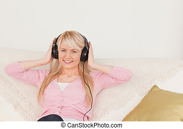 Good looking female listening to music on her headphones while sitting on a sofa in the living room