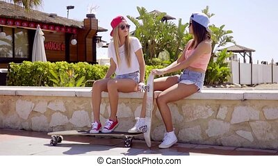 Good looking female skater friends sit on wall - Good...