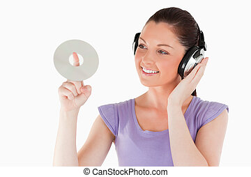Good looking female with headphones holding a CD while standing