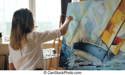 Good-looking girl artist is busy painting seascape on canvas...
