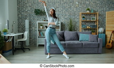 Good-looking girl in casual clothing dancing alone in ...