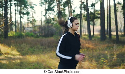 Good-looking girl is jogging in park and enjoying music in...