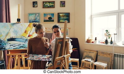Good-looking girl is learning to paint having class with experienced female teacher skillful painter, people are working and talking discussing visual arts.