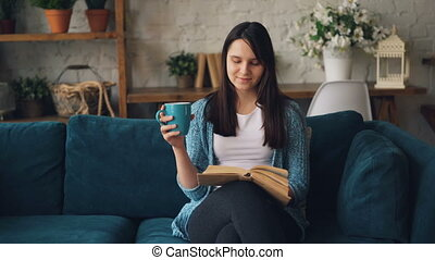 Good-looking girl is reading book sitting on sofa at home...