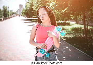 Good-looking girl is standing on street and holding skate in her hands. It is coloured by pink and blue colors. Girl is holding it with both hands and looking down to the side. She is enjoying music.