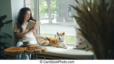 Good-looking girl stroking shiba inu dog and reading book in...