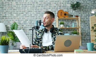 Good-looking guy reading information in microphone making...