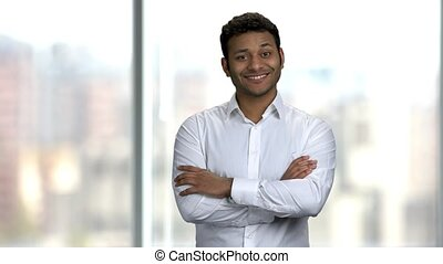 Good-looking Indian guy pointing at copy space. Indian businessman showing something at copy space on blurred background.