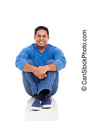 indian man sitting on floor isolated on white