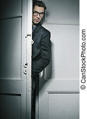 Good-looking man behind the door