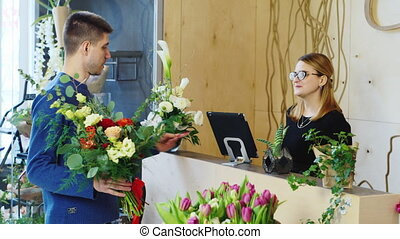 Good looking man buys a bouquet at a flower shop