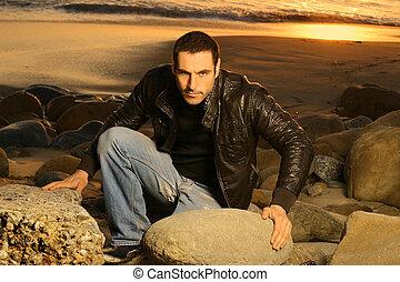 Good looking man climbing rocks at sunset