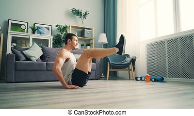 Good-looking man doing abdomen crunches different positions...