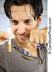 Good looking man smiling at cigarette ready to stop smoking