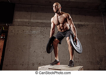 good looking man using barbell plates in cross training