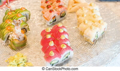 Tracking shot of delicious grilled fish and appetizing sushi...