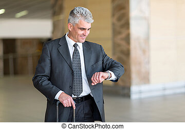 mid age businessman checking time at airport