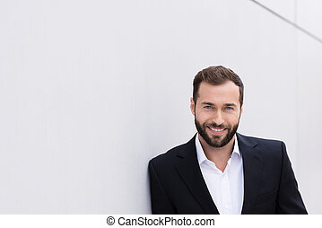 Smiling Good Looking Middle Age Man in Black and White Suit Leaning on White Wall.