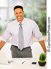 middle aged businessman standing by his desk