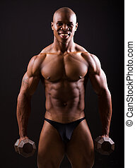 muscular black man holding two dumbbells