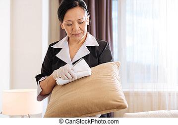 Good looking nice hotel maid holding a sofa cushion - It...